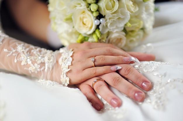 Buquê de flores do casamento em mãos de noiva com vestido branco