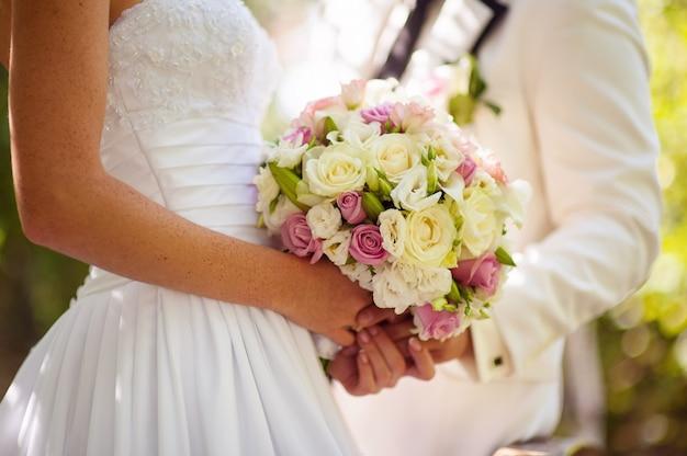 Buquê de flores do casamento em mãos de noiva e noivo