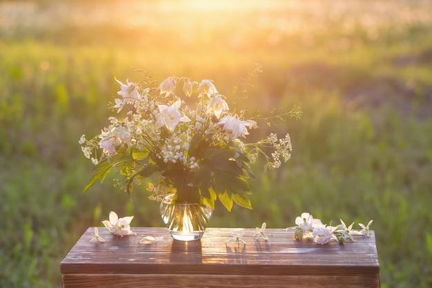 Buquê de flores do verão em um vaso de vidro na luz solar ao ar livre