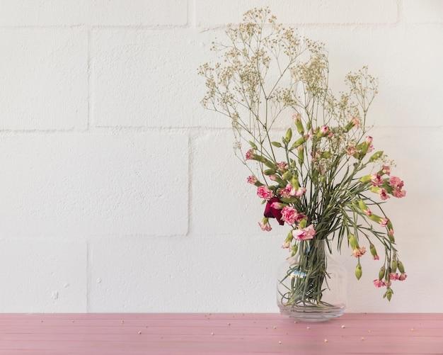 Buquê de flores e galhos de plantas em vaso perto da parede