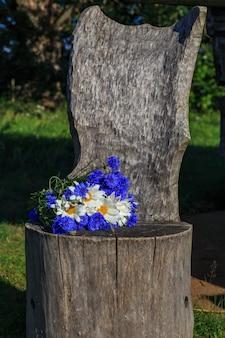 Buquê de flores e margaridas em uma cadeira de madeira velha no jardim