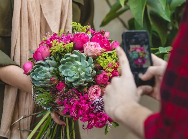 Buquê de flores e suculentas nas mãos de uma mulher, tiro móvel de lado