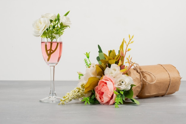 Buquê de flores e uma taça de vinho rosé na superfície cinza.