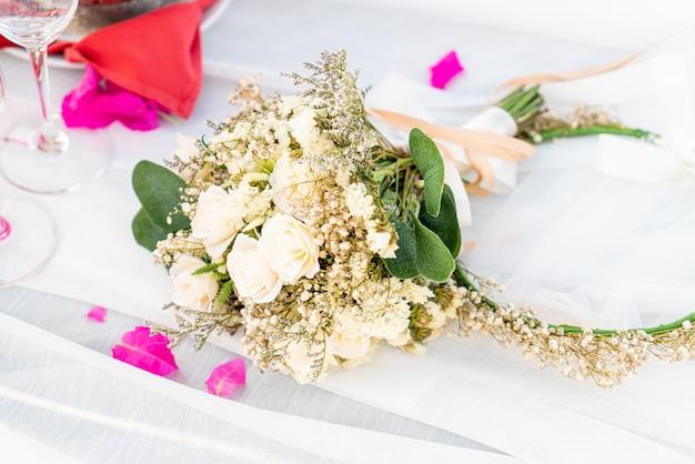 Buquê de flores e vidro e champanhe no arco de casamento