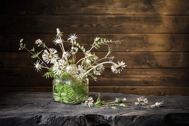 Buquê de flores em frasco de vidro com fundo escuro de madeira