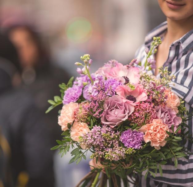 Buquê de flores em tons pastel e claro, abraçado por uma senhora na rua