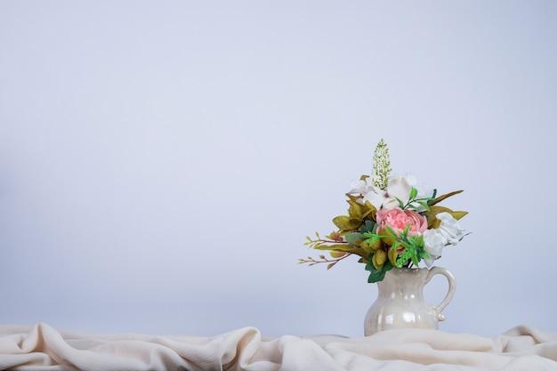 Buquê de flores em um vaso de cerâmica na parede escura.
