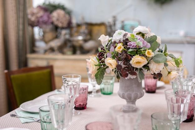 Buquê de flores em um vaso na mesa de casamento