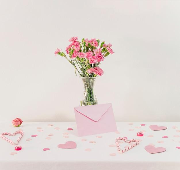 Buquê de flores em um vaso perto de conjunto de corações de papel, envelope e bastões de doces