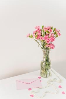 Buquê de flores em um vaso perto de envelope, corações de papel e miçangas na mesa