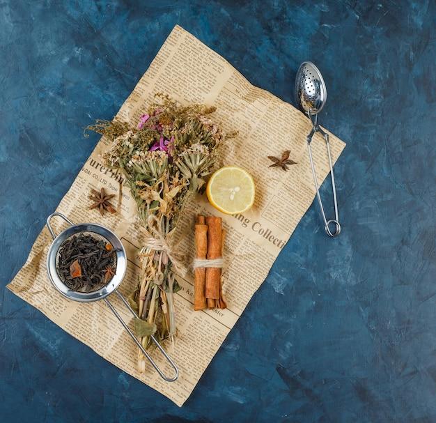 Buquê de flores em uma tábua de cortar com canela, limão e uma peneira de chá