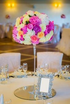 Buquê de flores em vaso de vidro na mesa de jantar