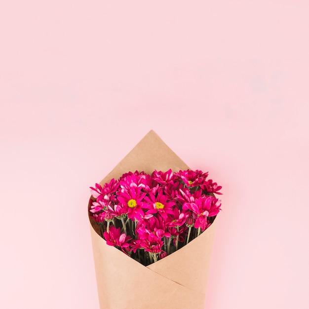 Buquê de flores embrulhado com papel marrom contra fundo rosa
