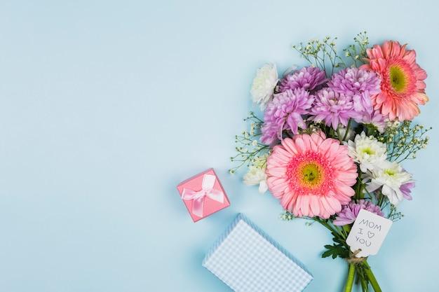 Buquê de flores frescas com título na tag perto de caixa de presente e notebook