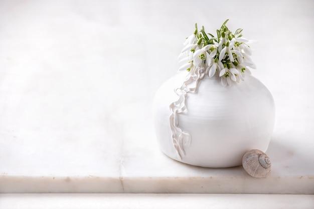Buquê de flores frescas da primavera de snowdrops em um vaso de porcelana branca com concha de caracol na mesa de mármore branco. composição da primavera