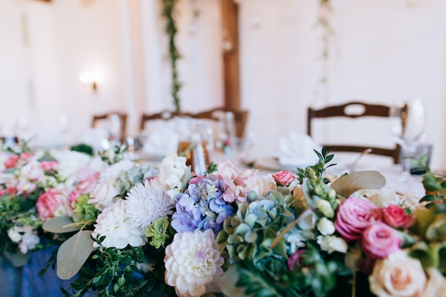 Buquê de flores frescas de rosa, brancas e azuis em cima da mesa do restaurante