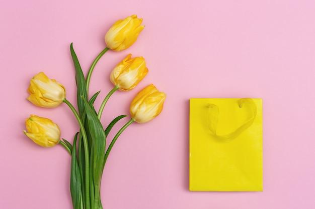 Buquê de flores frescas de tulipa e saco de papel amarelo em pano de fundo rosa. presente de primavera, fundo de férias com espaço de cópia. cores brilhantes e estilo minimalista. vista do topo.