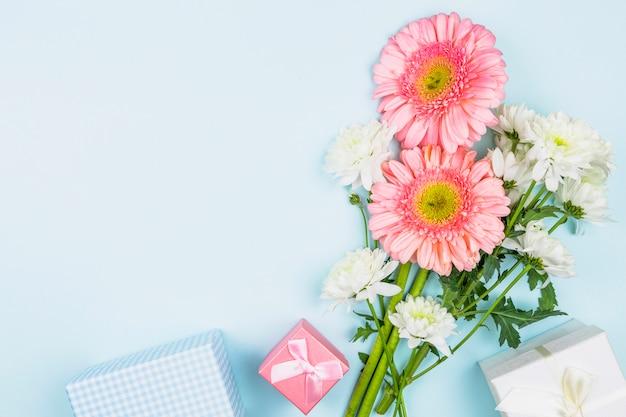 Buquê de flores frescas perto de caixas de presentes