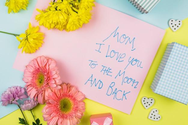 Buquê de flores frescas perto de papel com palavras, corações ornamentais e caixa de presente