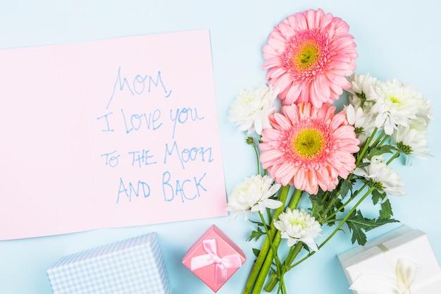 Buquê de flores frescas perto de papel com palavras e caixas de presentes