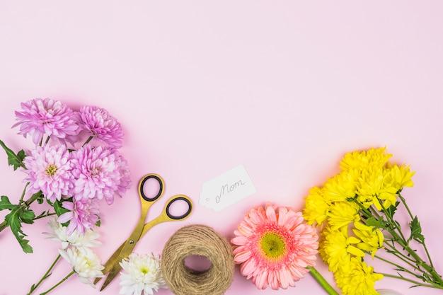 Buquê de flores frescas perto de tag com a palavra mãe e tesoura
