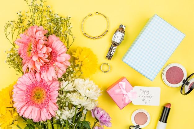 Buquê de flores frescas perto de tag com palavras de dia das mães feliz na caixa de presente e acessórios
