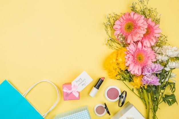 Buquê de flores frescas perto de tag com palavras de dia das mães feliz na caixa de presente e batons com pós