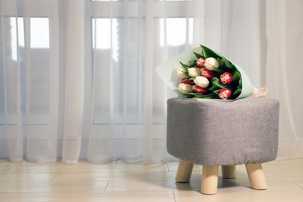 Buquê de flores frescas, tulipas vermelhas e brancas em uma poltrona cinza com pernas de madeira perto de uma janela de tule e piso de ladrilho