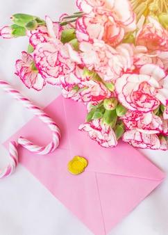 Buquê de flores grandes com envelope brilhante na mesa