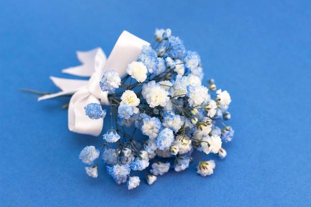 Buquê de flores gypsophila branco-azul. com um laço branco sobre um fundo azul.