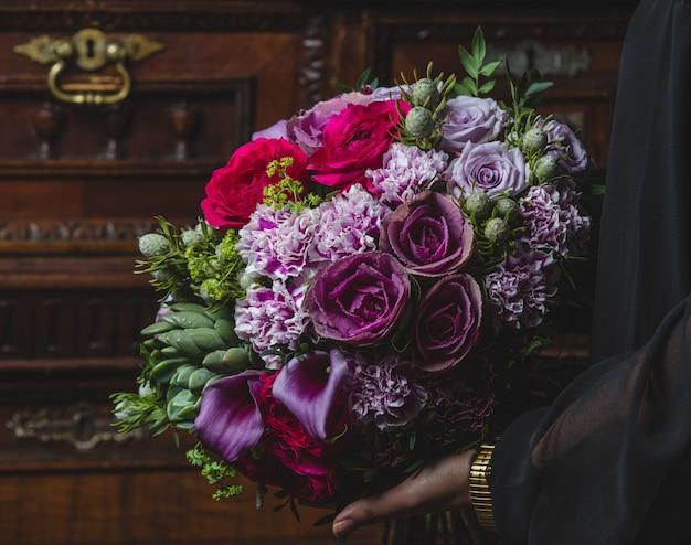 Buquê de flores holded por uma mulher na porta