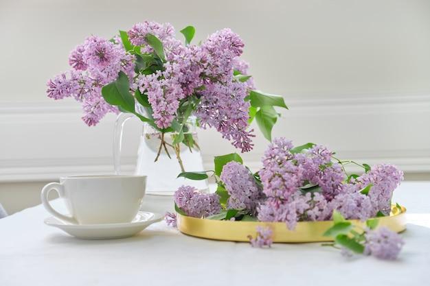 Buquê de flores lilás em jarra de vidro na mesa