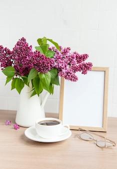 Buquê de flores lilás em um vaso e moldura vazia em uma mesa de madeira.