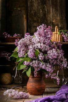 Buquê de flores lilás em uma panela de cerâmica na mesa antiga