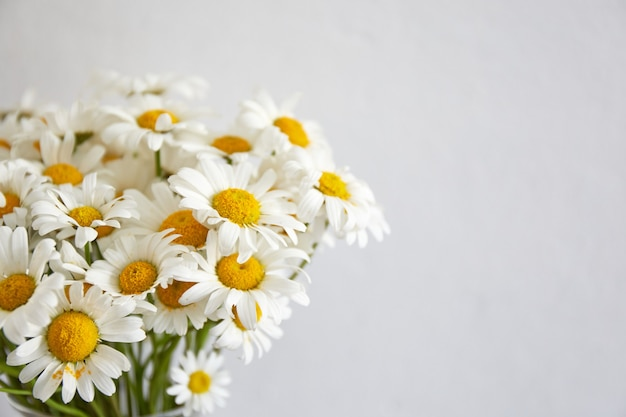 Buquê de flores margarida em vaso de vidro, ficar na placa de madeira. interior da casa.