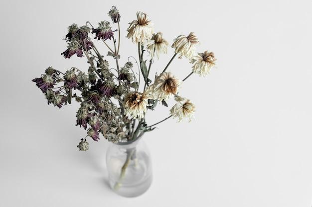 Buquê de flores murchas em uma parede branca
