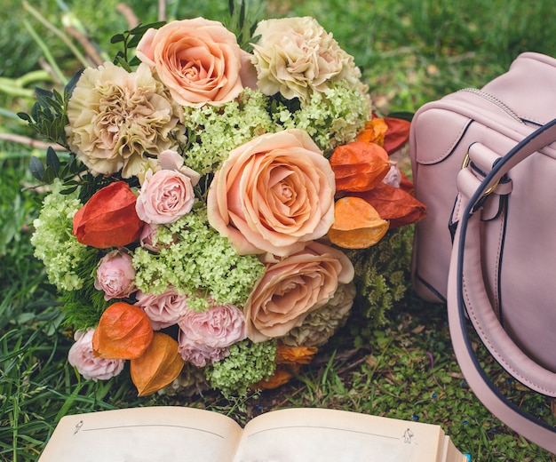 Buquê de flores na grama, sacola e um livro