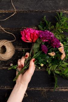 Buquê de flores na mão feminina em uma mesa de madeira preta
