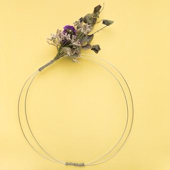 Buquê de flores no anel metálico vazio sobre o pano de fundo amarelo