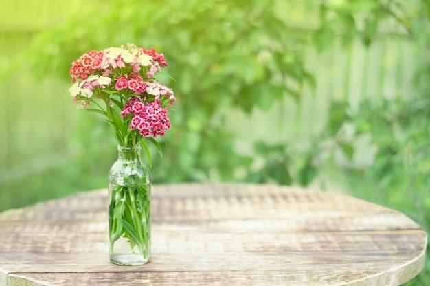 Buquê de flores no banco na mesa ao sol