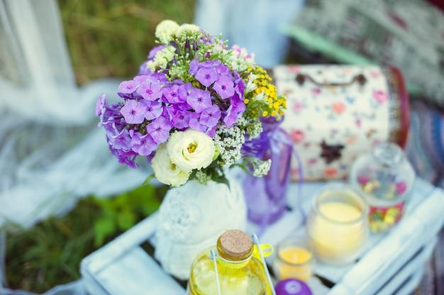 Buquê de flores no estilo boho em um vaso de vidro na natureza