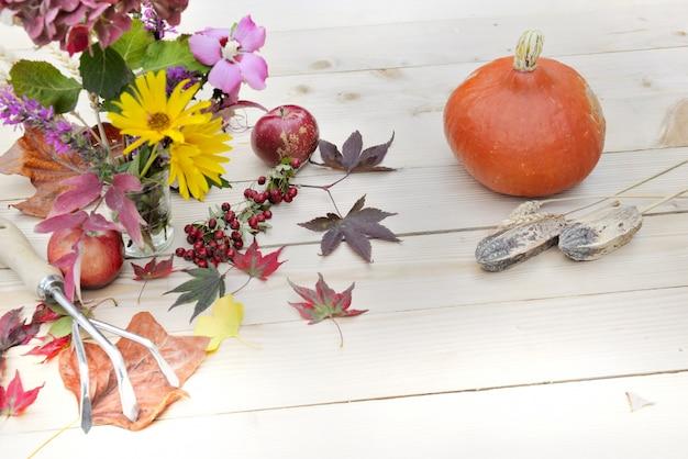 Buquê de flores outonais folhas maçãs vermelhas e abóbora em uma mesa de madeira