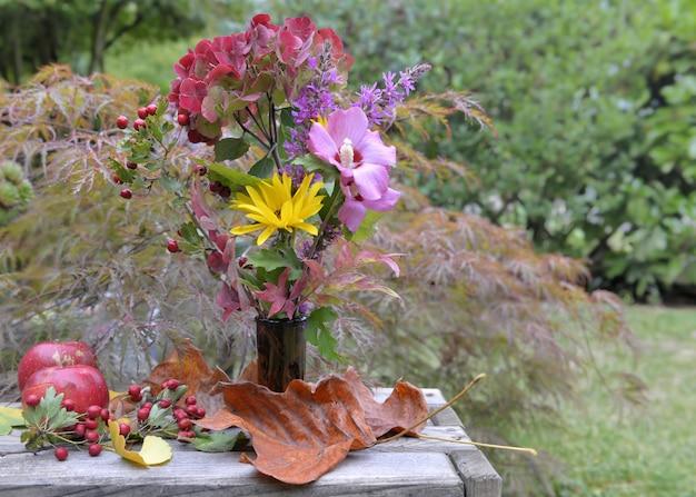 Buquê de flores outonais provenientes de jardim em uma mesa de jardim com maçãs e folhas