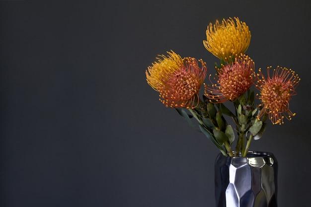 Buquê de flores protea exóticas amarelas e laranja em um vaso de metal em um fundo escuro