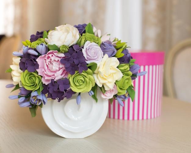 Buquê de flores rosa e caixa de presente na mesa de madeira