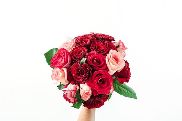 Buquê de flores rosa e vermelha na mão de uma mulher na superfície branca