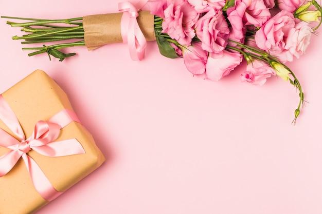 Buquê de flores rosa eustoma fresco e caixa de presente contra um fundo rosa