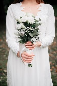 Buquê de flores rosas e ramos de eucalipto nas mãos da noiva.