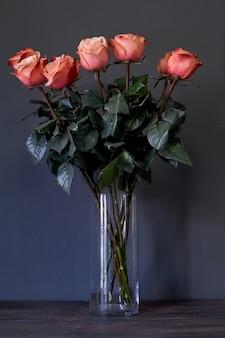 Buquê de flores rosas em um vaso de cristal alto claro contra uma parede cinza, foco seletivo