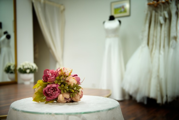 Buquê de flores rosas na mesa com rendas no salão de casamento perto de vestidos brancos esperando a noiva